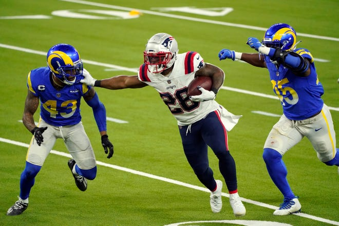 Patriots running back James White runs between Los Angeles free safety John Johnson, left, and Ogbonnia Okoronkwo during Thursday's game.