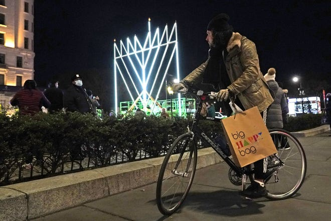 """A man on a bicycle pauses on the sidewalk along Fifth Avenue in Manhattan near what has been described as """"the world's largest Hanukkah menorah,"""" Dec. 10 in New York, on the first night of Hanukkah, the annual eight-day Jewish festival of lights. Because of coronavirus restrictions, a limited and socially-distanced crowd was allowed to attend."""