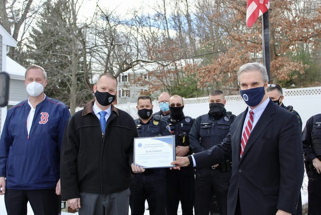 Auburn Police Det. Keith Chipman (second from left) receives a TEAM Award from Worcester District Attorney Joseph D. Early Jr. as fellow Auburn officers and Chief Andrew J. Sluckis (left) look on.