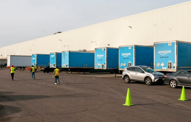 Trucks are parked in loading docks at the Amazon warehouse in Milford on Friday.