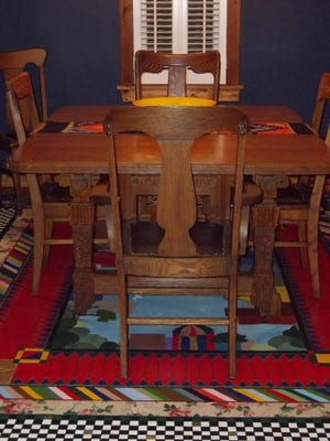 A colorful floorcloth provides easy-care protection as well as cheerful design and style to this family dining room.