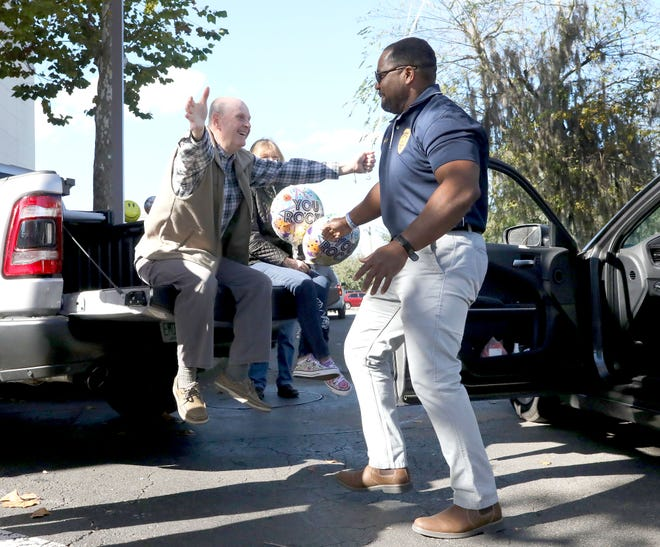 Bill Cervone, left, the retiring state attorney, opens his arms to give Chad Scott, the Alachua chief of police and a former employee, a hug during a surprise drive-by retirement celebration for Cervone on Friday.