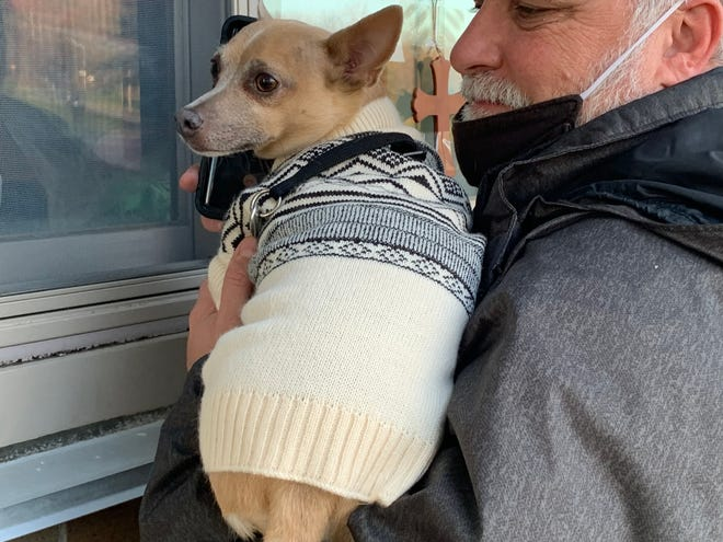 Steven Horton holds the family's dog, a Chihuahua named Lew, up to the window of his mother's isolation room at Valley View Nursing Home to lift her spirits during a socially distanced visit Dec. 10.