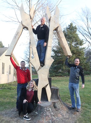 The team that worked on the carving of a triple set of pliers from a tree stump is Naomi Benson (front) and Chris Lane, Dan Warther and Cogan Warther. (TimesReporter.com / Jim Cummings)