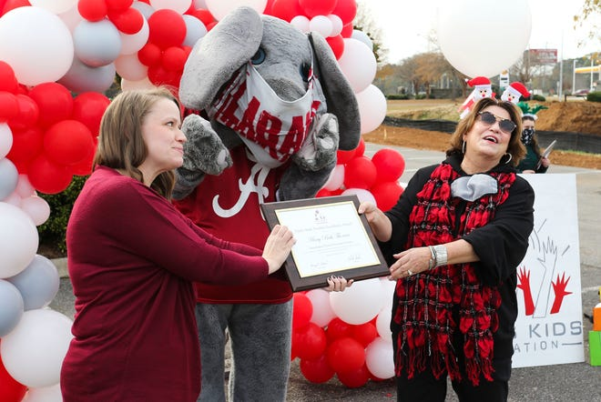 Mary Beth Thomas, from Huntington Place Elementary School, accepts her award from Terry Saban during a drive-by version of the 9th Annual Nick's Kids Foundation Teacher Excellence Awards Friday, Dec. 11, 2020, in Sokol Park. [Staff Photo by Gary Cosby Jr.]