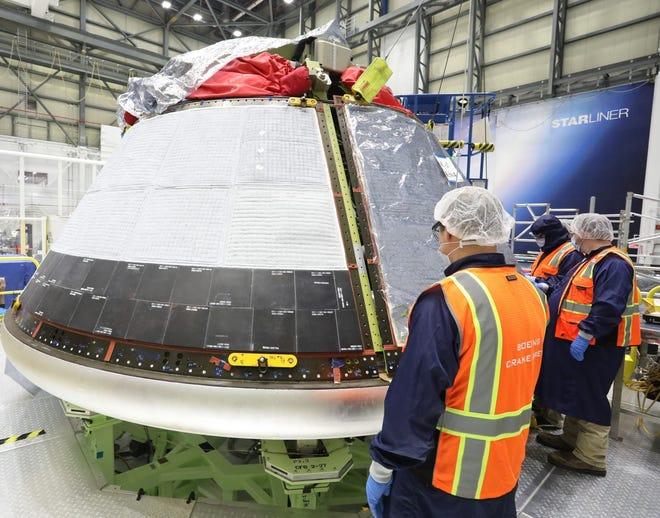 Starliner technicians finish installing back shells on the Orbital Flight Test-2 crew module at Starliner factory in Cape Canaveral, FL.