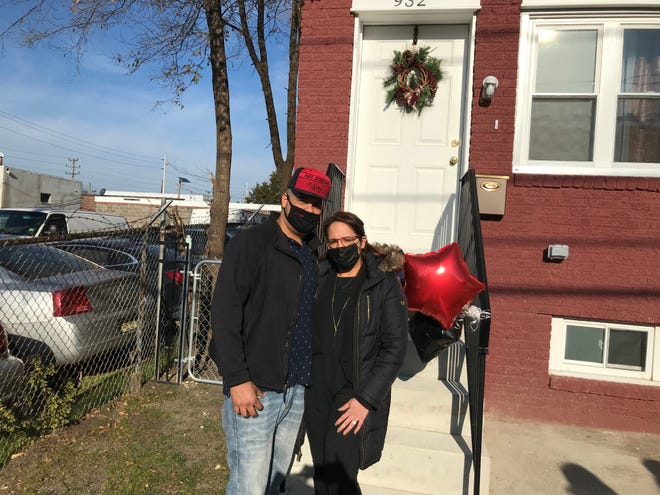 Wandy Gutierrez and Maxiell Acosta stand in front of their new home in Camden's Cramer Hill neighborhood.