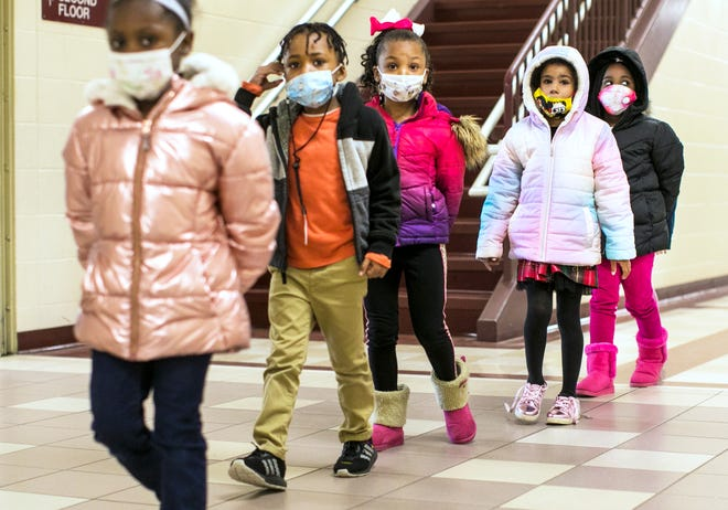 Students at Rosa Parks Elementary in Middletown, form a straight line to move through the building, Friday, Dec. 11, 2020. The school is on a hybrid scheduled due to the coronavirus pandemic and both students and teachers wear masks.