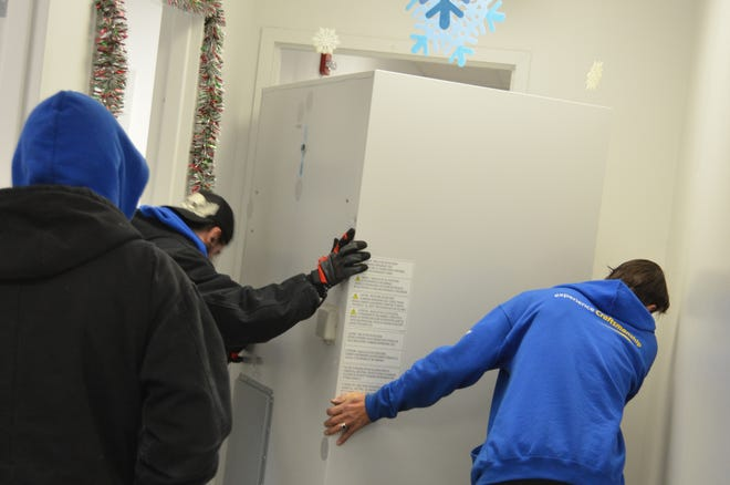 Workers prepare to install one of 10 medical grade laboratory freezers delivered Friday at Oakland County health facilities in anticipation of COVID-19 vaccine doses as soon as next week.