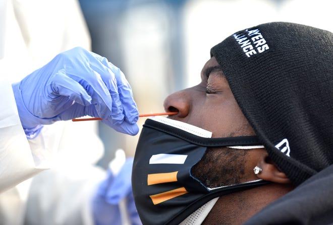 Pemain luar Chicago Cubs Cameron Maybin, mantan Detroit Tiger, mendapatkan tes usap nasofarengeal untuk COVID oleh Wayne Health RN Maya Johnson, kiri, dari Detroit.