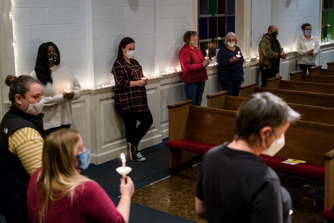 People listen to closing words from Stephen Ralph, not pictured, during the Homeless Memorial Service held at The Gathering Church in Downtown Evansville, Ind., Thursday night, Dec. 10, 2020. This year, attendees socially-distanced and wore masks and the service was live-streamed to limit the crowd size to help curb the spread of COVID-19.