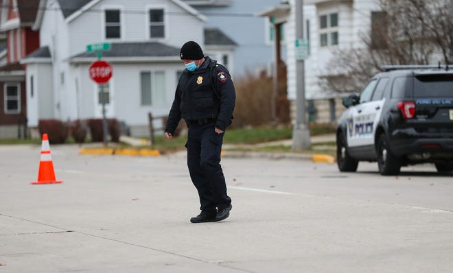 A Fond du Lac police officer searches Fifth Street between Main Street and Marr Street Friday morning for shell casings or bullets after being sent to the area to investigate reports of possible shots fired.