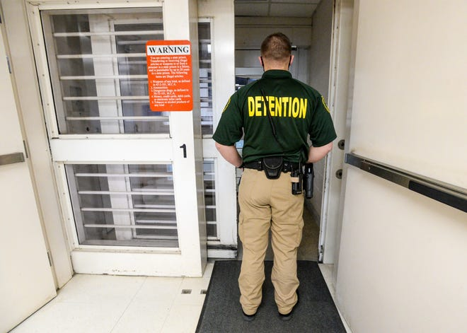 A detention officer waits for the security door to open while entering the Cascade County Jail in December 2020.