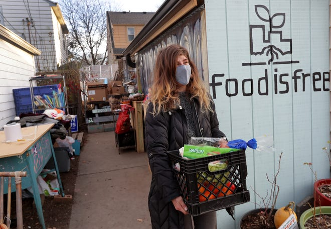 Emma Toth holds a basket of donated produce that was dropped off Dec. 10 at her Food is Free pantry in Milwaukee.