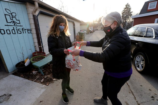 Julia Watts, right, stops by to give Emma Toth bags of donations on Dec. 10 at the Food is Free pantry. After serving as a resource for over a year, the pantry is now being asked to shut down.