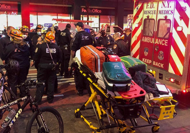 Emergency personnel respond to a scene where pedestrians were struck by a car during a protest Friday, Dec. 11, 2020, in New York. Witnesses say the protest march was passing through an intersection at around 4 p.m. when a car went into the crowd. The New York Fire Department says six people were hospitalized. Police and fire officials said the injuries didn't appear to be life-threatening. (AP Photo/David Martin)