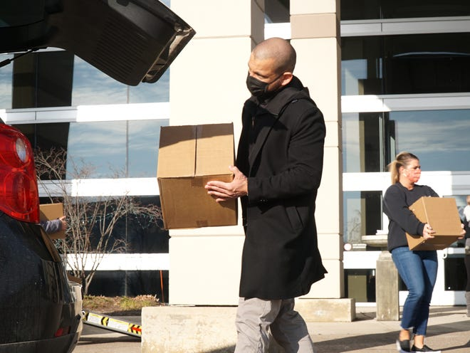 Sysco food system's Tom Batayeh helps to load a box of food into the trunk of a need restaurant worker's car on Dec. 10, 2020 at the Suburban Collection Showplace.
