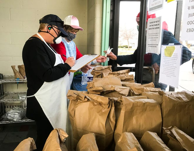 Volunteers Sandy Piotter and Chris D'Luge hand out meals to go on Thursday, Dec. 10, 2020, at Mid City Nutrition.