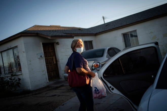 Norma Flores carries her groceries into her home in Henderson, Nev., Tuesday, Nov. 10, 2020. Flores is a Mexican immigrant who spent two decades working as a waitress at the Fiesta before COVID-19 descended and she lost her job. She lives in a concrete block house with six grandchildren, most of them doing school online. She dreads when she overhears a teacher asking what students had for their lunches and snacks. She rarely has enough food for both.