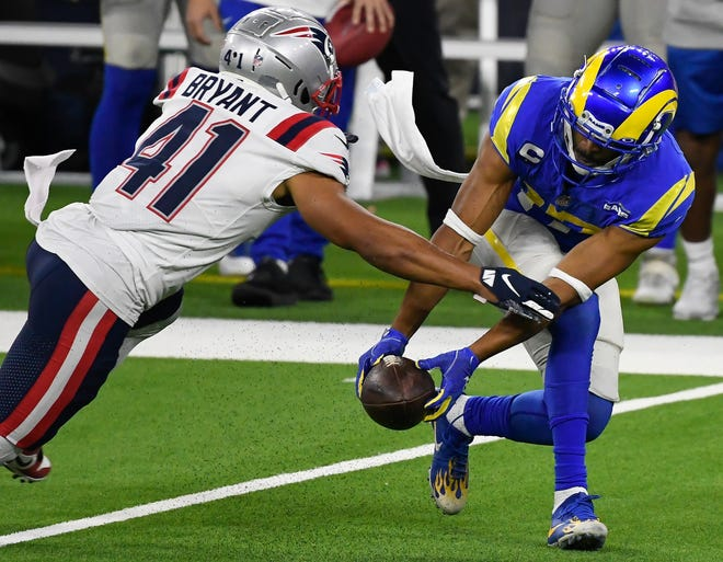 Los Angeles Rams wide receiver Robert Woods (17) makes a fingertip catch as New England Patriots cornerback Myles Bryant moves in to make the tackle.