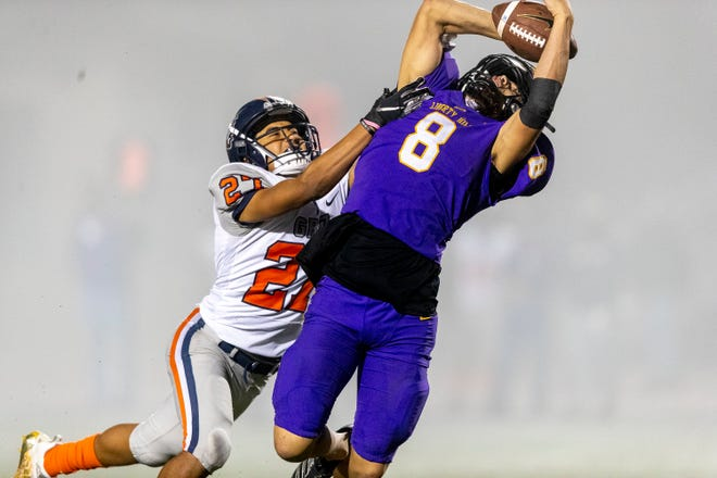 In the fog, Liberty Hill tight end Nathaniel Hilbrich pulls down a 27-yard reception over Glenn defensive back Sky Mendez during a 51-0 bidistrict playoff victory at Panther Stadium Friday.