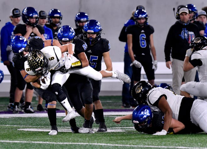 Wildcats running back Landon Smith is momentarily carried as he is tackled by Gunter defenders during Canadian's semifinal game in Abilene.