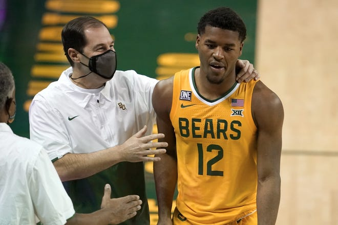 Baylor head coach Scott Drew, left, talks with guard Jared Butler (12) as he leaves the game late in the second half of an NCAA college basketball game against Stephen F. Austin in Waco, Texas, Wednesday, Dec. 9, 2020. (AP Photo/Tony Gutierrez).