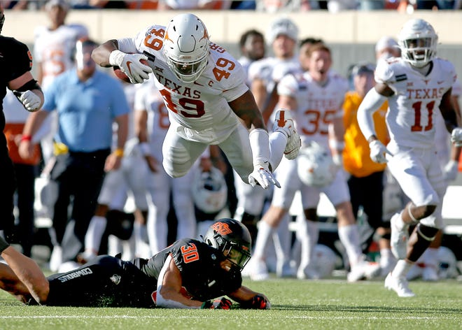 Texas' Ta'Quon Graham (49) is tripped up by Oklahoma State's Chuba Hubbard (30) at the end run on a fumble recovery in the second quarter during the college football game between the Oklahoma State University Cowboys and the University of Texas Longhorns at Boone Pickens Stadium in Stillwater, Okla., Saturday, Oct. 31, 2020. Photo by Sarah Phipps, The Oklahoman