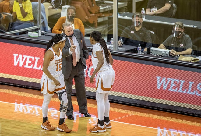 Texas coach Vic Schaefer speaks with guards Kyra Lambert (15) and Joanne Allen-Taylor (11) during a game against Louisiana Tech at the Erwin Center on Dec. 2 in Austin.