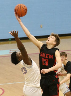 Salem's Drew Weir, right, and Alliance's Brandon Alexander during tipoff of their conference game at Alliance High School Friday, December 11, 2020.