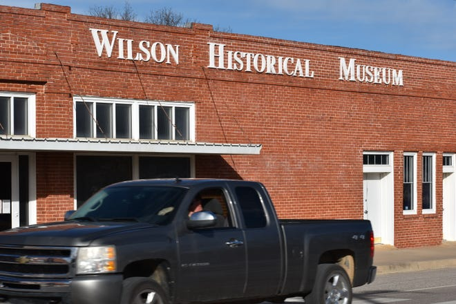 A pickup truck drives past the Wilson Historical Museum. While closed since the onset of a pandemic, the museum is still selling gift shop items online and providing research assistance over the phone.