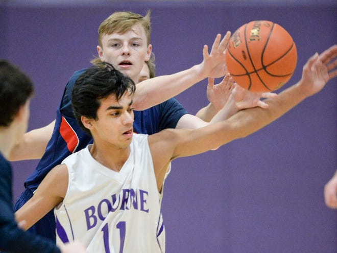 Coleman Moynihan of Apponequet looks to pass pressured by Muhammad Khan of Bourne in a game in December 2019.  Bourne and 14 other Cape Cod and island schools will compete in boys and girls basketball, with most also offering boys and girls ice hockey, plus swimming and diving and gymnastics.