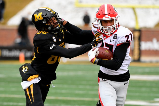 Georgia defensive back Eric Stokes (27) runs with the ball after intercepting a pass as Missouri wide receiver Tauskie Dove (86) defends during a game Saturday at Faurot Field.