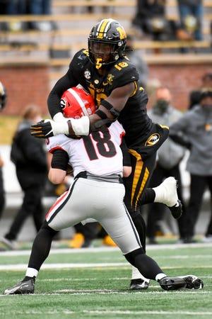 Missouri defensive lineman Trajan Jeffcoat, top, sacks Georgia quarterback JT Daniels during a game last season at Faurot Field.
