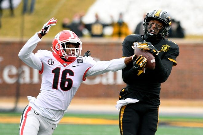 Missouri wide receiver Damon Hazelton, right, catches a pass as Georgia defensive back Lewis Cine (16) defends during a game Saturday at Faurot Field.
