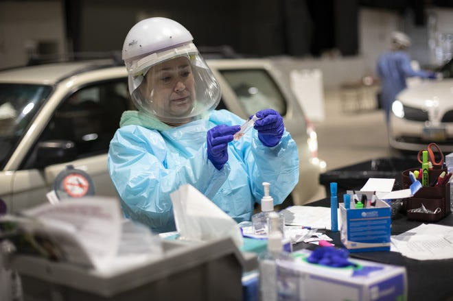 Mount Carmel registered nurse Vanessa Keller labels a vial after administering a COVID-19 test in the Columbus Public Health drive through testing site at the Ohio State Fairgrounds in Columbus on Tuesday, Dec. 8, 2020.