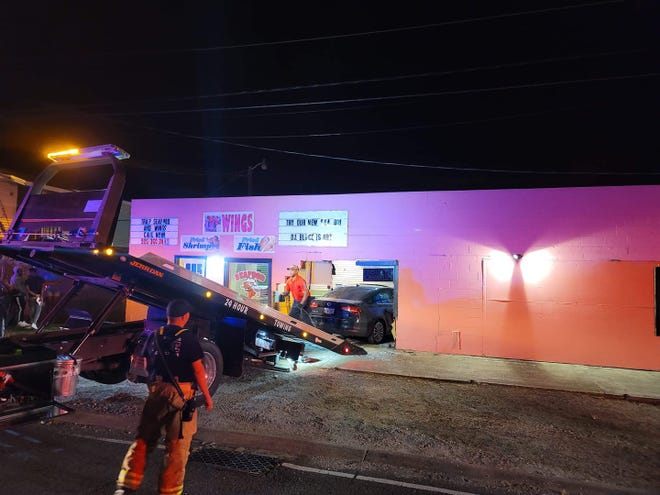 Crews work to pull a car after it crashed into a Houma wing shop.