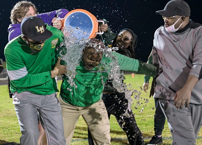 Lake Minneola head coach Walter Banks is doused with water after the Hawks beat St. Augustine 49-48 in triple overtime in the Class 6A state semifinals Friday at the Hawks Nest in Minneola. [PAUL RYAN / CORRESPONDENT]
