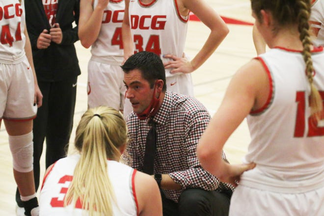DCG girls head basketball coach Adam Jones talks to his team during a timeout on Friday, Dec. 11 against Grinnell.