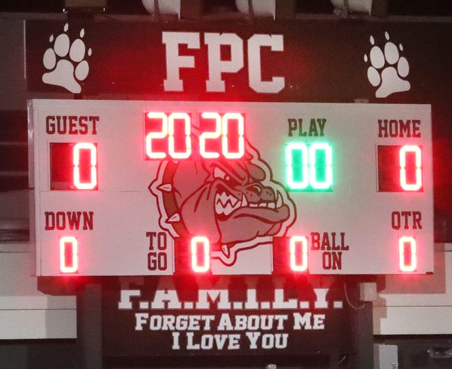 The Flagler Palm Coast High School scoreboard shows 20 minutes, 20 seconds, Friday December 11, 2020, during a drive-through memorial service for Principal Tom Russell who died after contracting COVID-19.