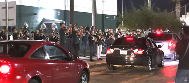 The Flagler Palm Cost High School band performs as a line of cars snakes through the parking lot, Friday December 11, 2020 during a drive-through memorial service for Principal Tom Russell who died this week from COVID-19.