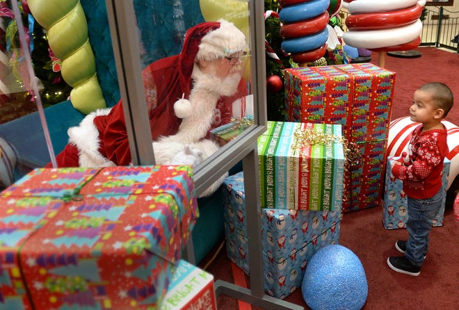 Jacob Nieves, 2, of Erie talks with Santa Claus at the Millcreek Mall in Millcreek Township. Santa, portrayed by Lenny Chatt, 73, of Lawrence Park, was seated behind a sheet of plexiglass due to COVID-19 safety measures. [Jack Hanrahan/Erie Times-News]