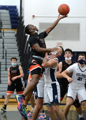 Cathedral Prep's Tavion Spencer, left, shoots over McDowell's Mason Beck in the District 10 boys basketball game Friday night at McDowell's Paul Goll Gymnasium.