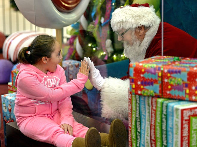 Maddie Brooks, 7, of Canadohta Lake, visits with Santa Claus Saturday at the Millcreek Mall in Millcreek Township. Santa, portrayed by Lenny Chatt, 73, of Lawrence Park, was seated behind a sheet of plexiglass due to COVID-19 safety measures.