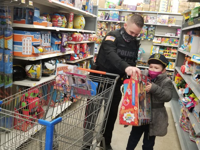 Officer Jimmy Giglio of the Canisteo Police Department helps shopper Leah load a toy into their cart during Saturday's Shop with a Cop event at Walmart in Hornell.