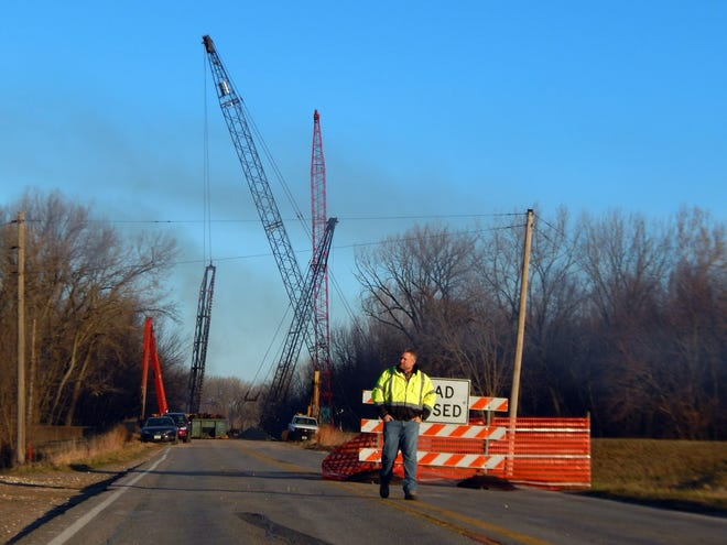 In this file photo, Des Moines County engineer Brian Carter walks along Des Moines County 99 south of Flint Creek; in the background are construction cranes belonging to Iowa Bridge and Culvert, the company replacing the bridge over Flint Creek.
