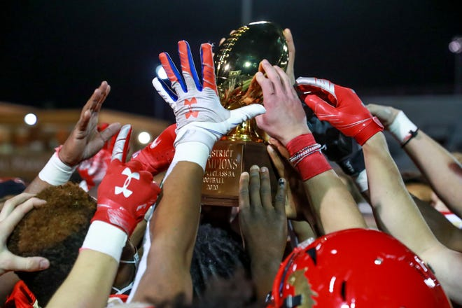 Coronado players celebrate with the trophy after the win against El Paso Bel Air during the Class 5A, Division I Bi-district Championship on Friday, Dec. 11, 2020, at Plains Capital Park at Lowrey Field in Lubbock, Texas.