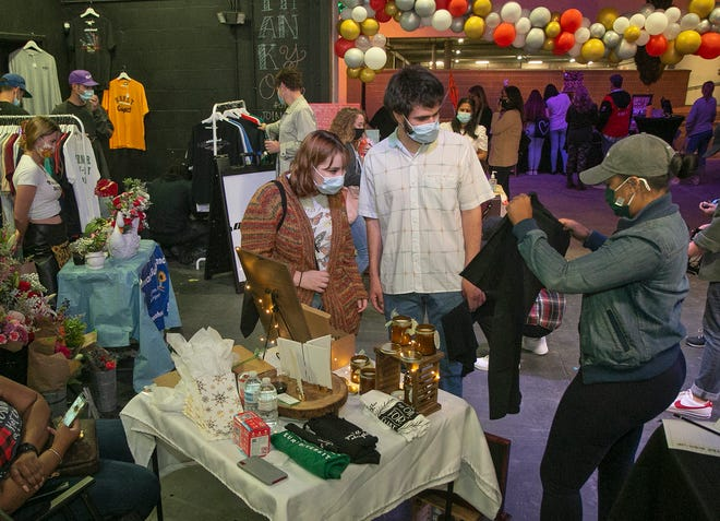 Candace Cole, right, owner of the pop-up shop Therame Self-Care Products & Gifts, shows Kyley Barclay and Nicholas Ohrmund items for sale during the Buena Market Holiday Weekend at LKLD Live in downtown Lakeland Friday night.
