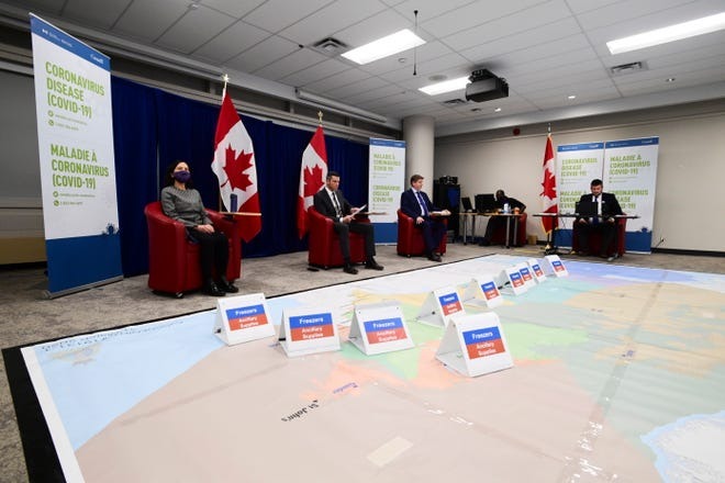 Chief Public Health Officer Dr. Theresa Tam, left, and Major-General Dany Fortin, second from left, join other members of the vaccine distribution task force as the Canadian Armed Forces and the Public Health Agency of Canada (PHAC) hold a rehearsal of concept drill for the COVID-19 vaccine rollout at the PHAC headquarters in Ottawa on Thursday.