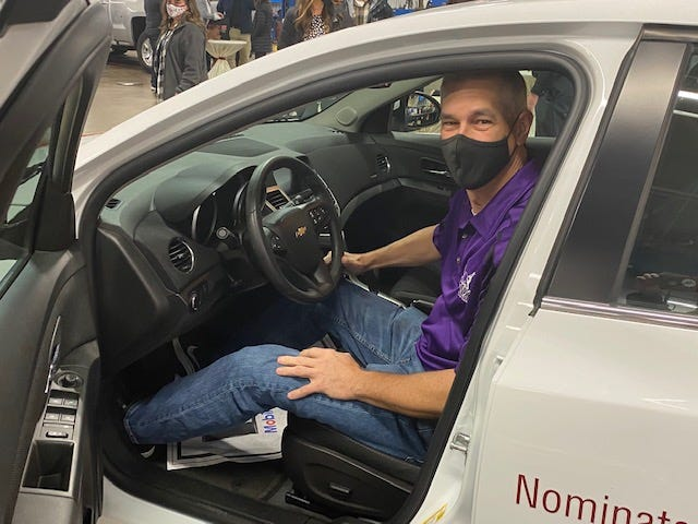 Eric Grunder sits in the car he won Saturday at the Amazing Teacher ceremony at Graue, Inc.